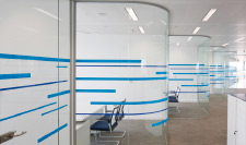 What are the benefits of glass partitions in an office?